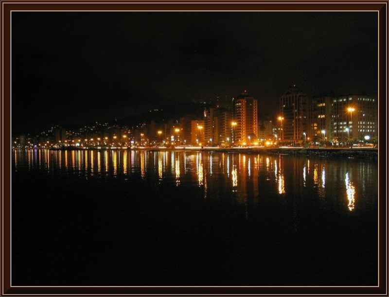 Florianópolis vista a noite, as luzes refletindo nas agua do mar.